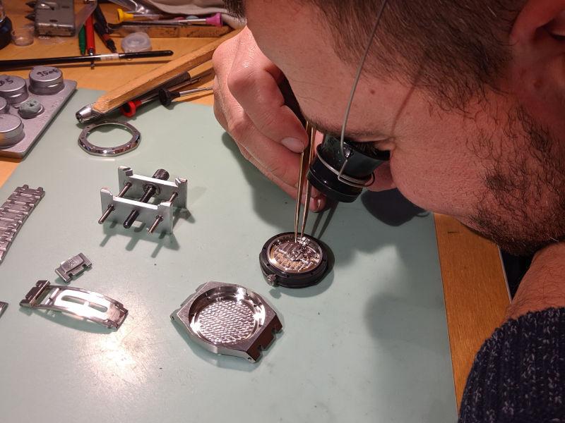 Photo d'un horloger expertisant une montre